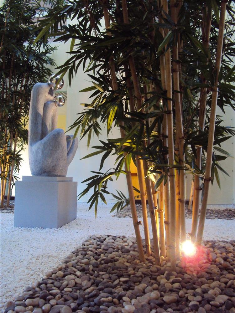 Installation d'un jardin zen à l'interieur d'un atrium. Bouquets de bambous de 4m de hauteur, troncs naturels, feuillage tissu polyester. Effet de graviers de différentes couleurs.<br />