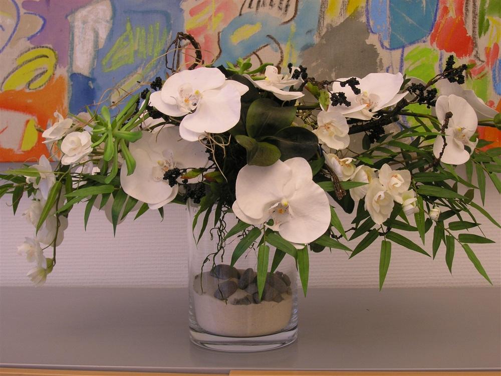 Bouquet d'orchidées blanches, feuillage de bambou et graines en tissu. Vase en verre, sable et galets. Composition pour bureau d'une banque privée.<br />
